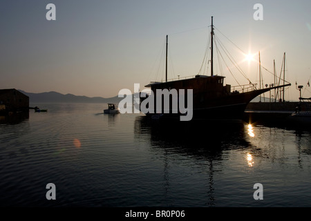 A boat is silhouetted against a low, summer sun in the port on the island of Iz in the Adriatic, Croatia. - Stock Photo