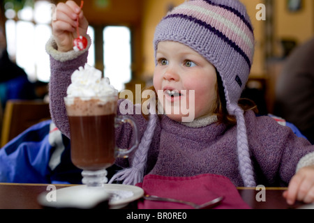 A young girl drinks hot chocolate during a break from skiing at Sunday River in Bethel, Maine. - Stock Photo