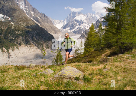 A man running in the French Alps above the Mer de Glace near Chamonix France. - Stock Photo