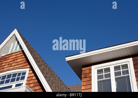 Upper story of a house against a deep blue sky. Shingled gable and dormer of a modest home.  Ottawa, Ontario, Canada - Stock Photo
