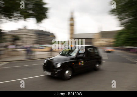 Taxi at speed in Parliament Square, Westminster, London - Stock Photo