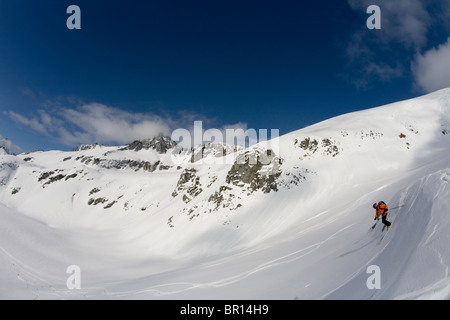 Man telemark skis down hill in Canada backcountry near Alaska Canada border. - Stock Photo