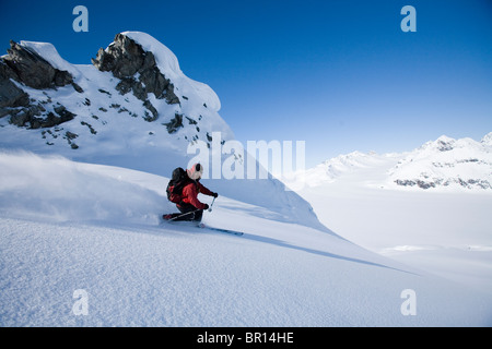 Man telemark skis down hill in Alaska backcountry near Canada border - Stock Photo