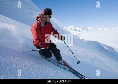 Man telemark skis down hill in southeast Alaska backcountry near Canada border. - Stock Photo