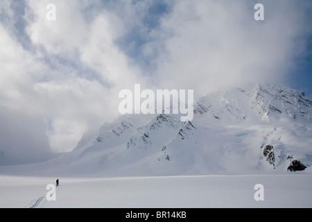 Backcountry skier crosses glacier under late day stormy sky. - Stock Photo