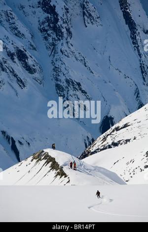 Man telemark skis down hill in Alaska backcountry near Alaska Canada border - Stock Photo