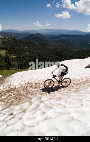 A man riding a mountain bike across snow on Donner summit in California. - Stock Photo