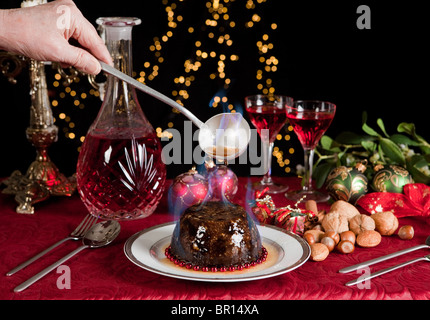 Christmas dinner table with xmas pudding as dessert - Stock Photo
