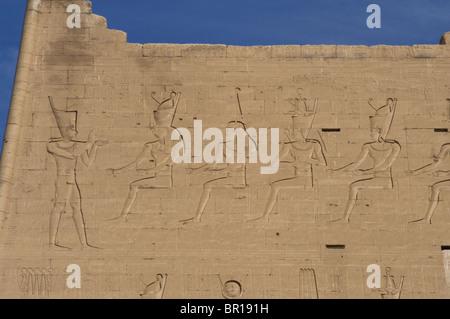 Temple of Horus. Pharaoh before gods. Main entrance. First pylon. Detail. Edfu. Egypt. - Stock Photo