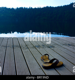 Pair of flipflop on a pontoon at the edge of a lake. - Stock Photo