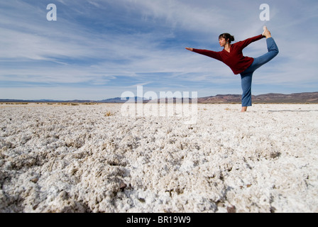 A young woman does yoga on a barren saltflat in Western Nevada. - Stock Photo