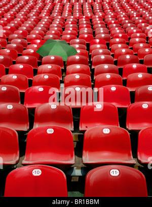 green umbrella left between red seats of bleachers