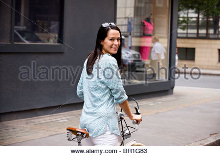 A young woman on a bicycle, smiling - Stock Photo