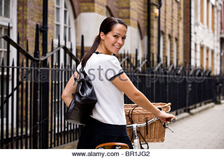 A young woman pushing her bicycle, smiling - Stock Photo
