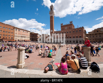Tourists visit 'Il Campo', the central square at the old town of Siena in Tuscany, Italy. - Stock Photo