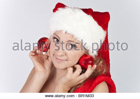 girl in the hat of Santa Claus holding Christmas balls as earrings - Stock Photo