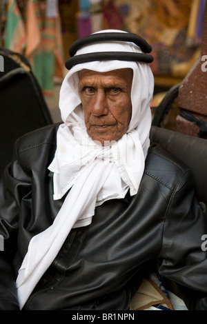 Portrait of adult Arab seller in a outdoor market wearing a leather jacket and Saudi white Ghutraon in Dubai. - Stock Photo