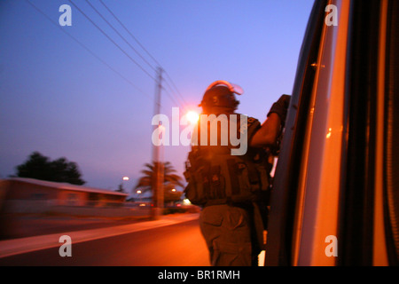 Las Vegas SWAT police officer hanging onto the side of an attack van whilst driving through the streets at night. - Stock Photo