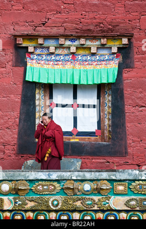 Tibetan Buddhist monk talks on cellular phone outside main temple, Tagong Monastary, Sichuan Province, China - Stock Photo