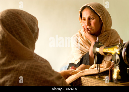 Two women chat while they do their sewing work in a Kabul business. - Stock Photo