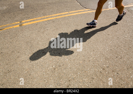 Shadow and feet of a runner in a marathon in San Francisco, California. - Stock Photo