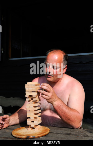 Mature Man playing a tricky board game - Stock Photo