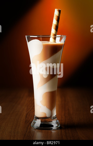 Chocolate smoothie drink in decorated tall glass with spiral wafer straw - Stock Photo