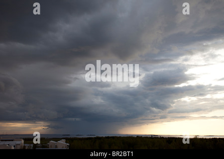 Rainstorm clouds rising from horizon . A local storm cell over sea. - Stock Photo