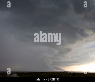 Rainstorm clouds rising from horizon - Stock Photo