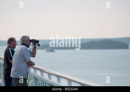 Two men stood viewing the archipelago islands in Stockholm, Sweden from a cruise ship with one man using a pair - Stock Photo