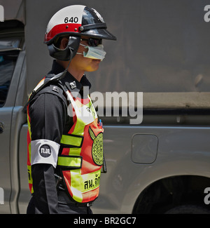 Thai police officer wearing an anti pollution mask in Bangkok's high pollution traffic flow. S. E. Asia - Stock Photo