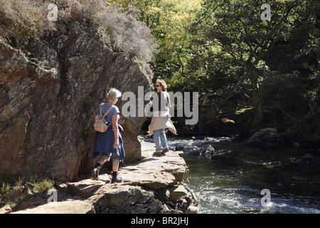 Women tourists walking on narrow rocky outcrop on Fishermen's Path by Afon Glaslyn River gorge in Aberglaslyn Pass. - Stock Photo