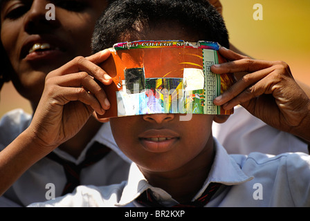 Indian schoolboyt shielding his eyes from the sun's glare during a solar eclipse. Cochin, India - Stock Photo