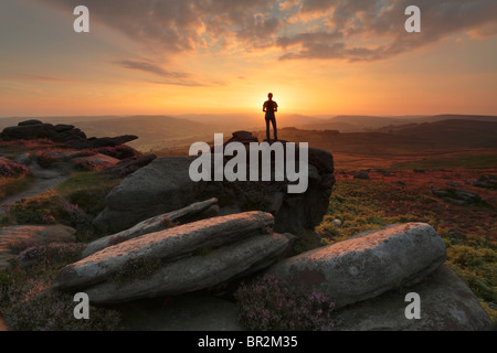 Silhouette of a woman standing on a rocky outcrop of Owler Tor near Hathersage in the Peak District of Derbyshire, - Stock Photo