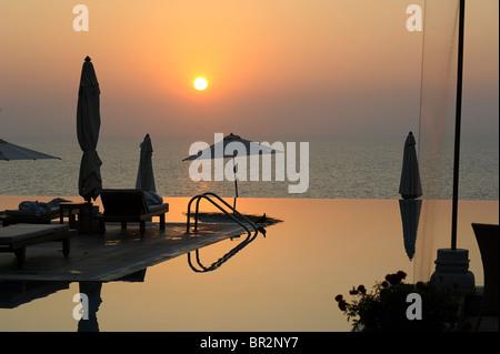 Hotel infinity pool at sunset, Kovalam, Kerala, India - Stock Photo