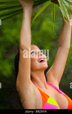 Young woman in bikini standing underneath palm leaf in the rain - Stock Photo
