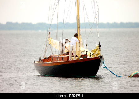 Two men putting down sails on sailboat - Stock Photo
