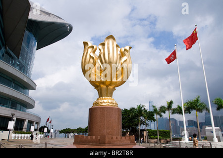 Golden Bauhinia sculpture with flags of Hong Kong and China in front of the Exhibition Center - Stock Photo