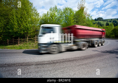 Big truck with trailer speeding on a road, with motion blur - Stock Photo