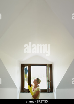 mid adult woman wiping windows in mansard. Vertical shape, waist up, copy space - Stock Photo