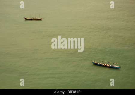 Two small traditional Ghanaian fishing boats at anchor in calm midday waters off the shore of  Cape Coast. - Stock Photo