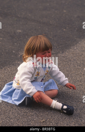 little girl crying and sitting on the ground - Stock Photo