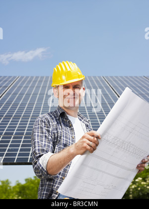 engineer holding blueprints in solar power station - Stock Photo