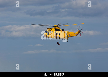 RAF Sea King rescue helicopter, lowers a winchman on to a waiting RNLI inshore lifeboat. - Stock Photo