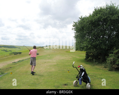 Male golf player teeing-off golf ball at beautiful golf course in Cotswolds - Stock Photo