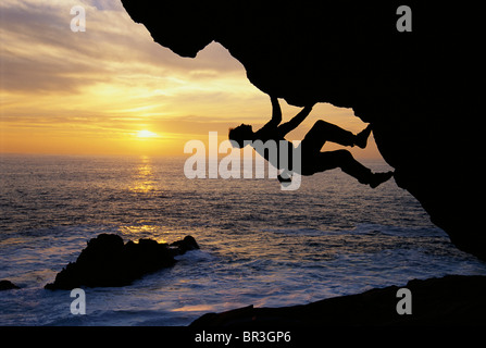 Climber silhouetted over the ocean at sunset - Stock Photo