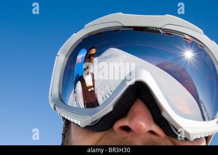 Snowboarder Troy Heithecker is reflected in skier Will Wacker's ski goggles on sunny day in the Canadian backcountry, - Stock Photo