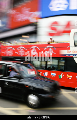 Taxi and sightseeing bus travelling through Piccadilly Circus, London - Stock Photo