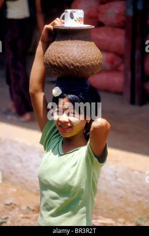 Woman wearing thanaka face paste sells drinking water to passengers at a rural station in Burma - Stock Photo