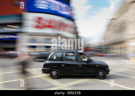 London taxi at speed through Piccadilly Curcus, London - Stock Photo